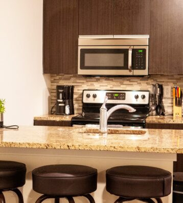 Kitchen Apartment showing small appliances, fridge, stove , microwave and seating stools