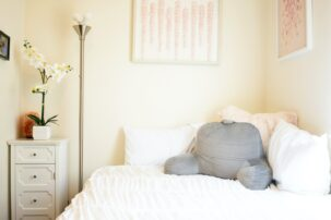 Drawer with flowers and bed with gray pillow in apartment